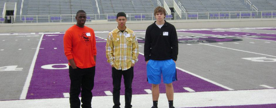 JC, Bruce Brookins, & Chris Hinckley standing on Estes field on their visit to UCA